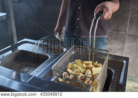 Unrecognizable Male Chef Deep-fries Potato Slices. Canteen Of Hotel. Industrial Kitchen. Man Fries P