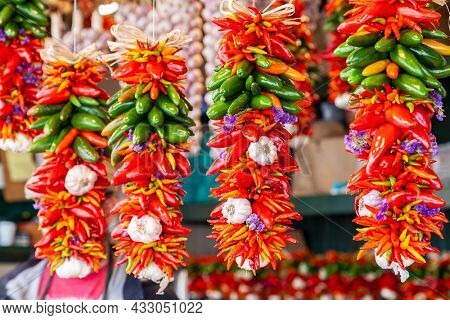 Colorful Fresh Red and Green Chillies, Chili Peppers, Chillis and Garlic Cloves Display Hanging For Sale in a Market