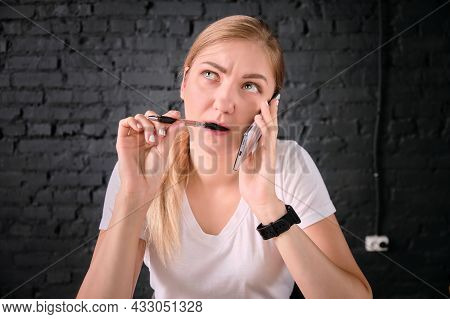 Young Adult Caucasian Woman Is Talking On Mobile Phone With A Thoughtful Look And Biting Pen. Woman