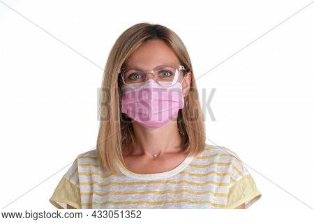 Portrait Of Young Woman In Pink Protective Medical Mask And Glasses For Vision