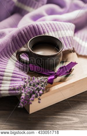 Morning Coffee. A Cup Of Coffee On A Warm Sweater Against The Background Of A Bouquet Of Lavender Fl
