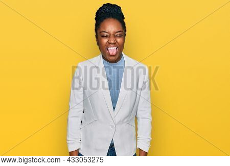 Young african american woman wearing business clothes sticking tongue out happy with funny expression. emotion concept.