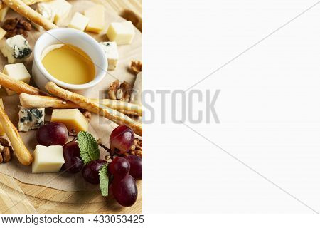 Cheese Platter On A Wooden Board With Honey And Grapes. Delicious Appetizer And Starter. Isolated On