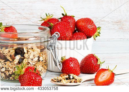 Granola In A Jar And Fresh Strawberries On A Wooden Background.