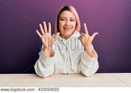 Hispanic woman with pink hair wearing casual sweatshirt sitting on the table showing and pointing up with fingers number seven while smiling confident and happy.
