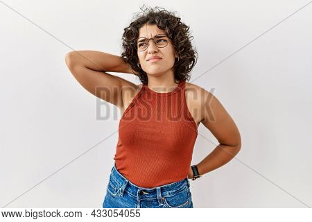 Young hispanic woman wearing glasses standing over isolated background suffering of neck ache injury, touching neck with hand, muscular pain