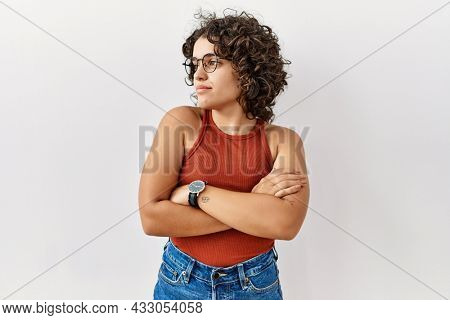 Young hispanic woman wearing glasses standing over isolated background looking to the side with arms crossed convinced and confident