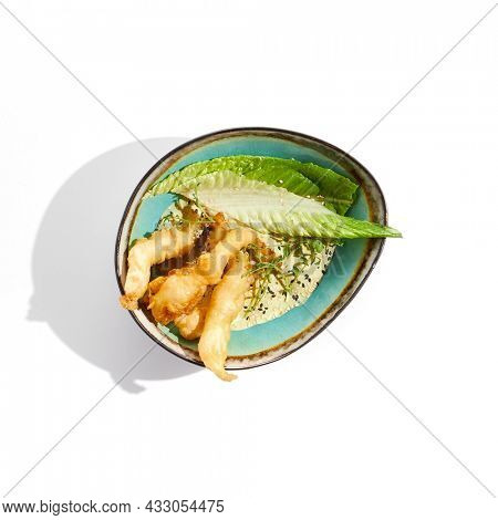 Delicious appetizers - tempura shrimp with peanut sauce. Japanese dish - crispy deep fried prawn. Tempura prawn with asian sauce isolated on white background. Hot deep fried seafood appetizer