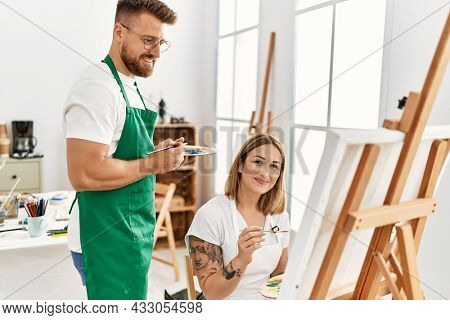 Young caucasian couple smiling happy drawing at art studio. Man standing and looking draw canvas.