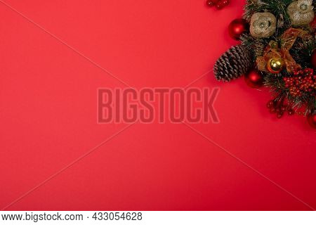 Composition of christmas decorations with pine cones and copy space on red background. christmas, tradition and celebration concept.