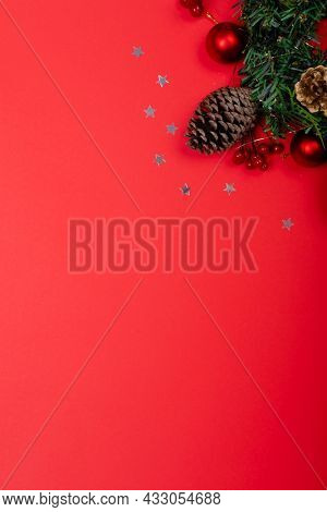 Composition of christmas decorations with pine cones, stars and copy space on red background. christmas, tradition and celebration concept.