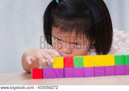 Child Little Girl Playing Wooden Toys At Home Or Kindergarten School. Kid Is Seriously Sorting And B