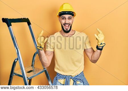 Handsome man with beard by construction stairs wearing hardhat shouting with crazy expression doing rock symbol with hands up. music star. heavy music concept.