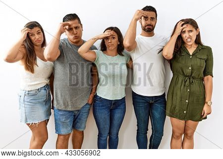 Group of young hispanic friends standing together over isolated background worried and stressed about a problem with hand on forehead, nervous and anxious for crisis