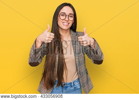Young hispanic girl wearing business clothes and glasses success sign doing positive gesture with hand, thumbs up smiling and happy. cheerful expression and winner gesture.