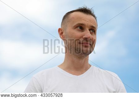 Young Smile Man Against The Blue Sky