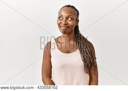 Black woman with braids standing over isolated background smiling looking to the side and staring away thinking.