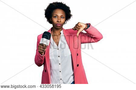 African american woman with afro hair holding reporter microphone with angry face, negative sign showing dislike with thumbs down, rejection concept