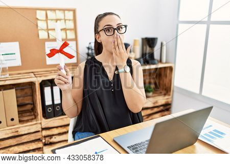 Young brunette woman holding graduate degree diploma at the office covering mouth with hand, shocked and afraid for mistake. surprised expression
