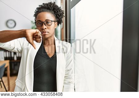African business woman working at the office with angry face, negative sign showing dislike with thumbs down, rejection concept