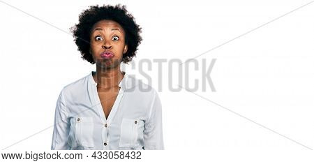 African american woman with afro hair wearing casual white t shirt puffing cheeks with funny face. mouth inflated with air, crazy expression.