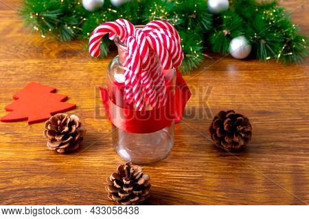 Composition of christmas decorations with candy canes, pine cones and garland on wooden background. christmas, tradition and celebration concept.