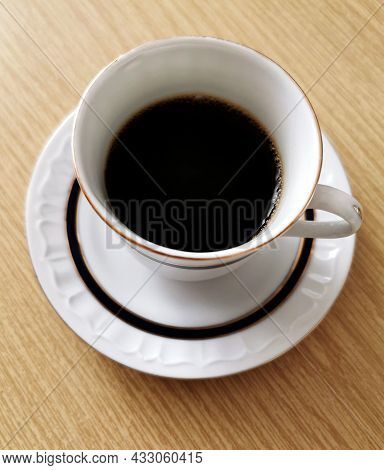Top View Image Of A Cup Of Black Coffee On A Wooden Table