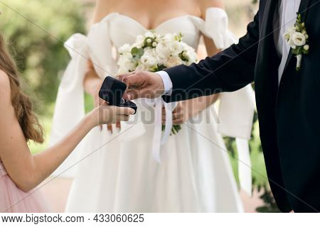 Wedding Traditional Ceremony Of The Bride And Groom. A Beautiful Groom Takes Wedding Rings To Put On
