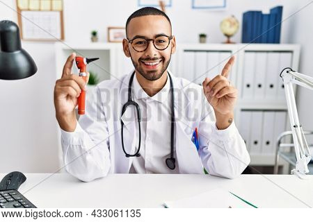 African american doctor man holding ear otoscope at the clinic smiling happy pointing with hand and finger to the side