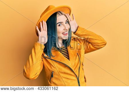 Young modern girl wearing yellow hat and leather jacket smiling cheerful playing peek a boo with hands showing face. surprised and exited