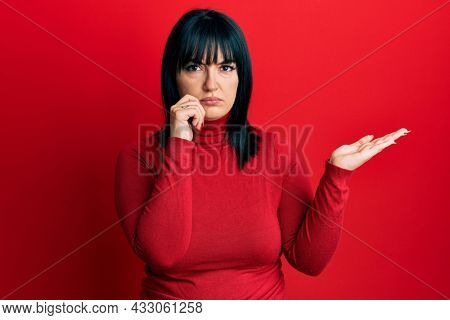 Young hispanic woman presenting with open palms, holding something skeptic and nervous, frowning upset because of problem. negative person.