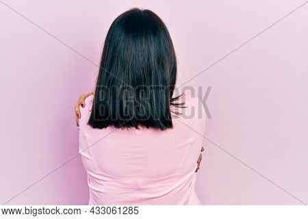Young hispanic woman wearing casual clothes hugging oneself happy and positive from backwards. self love and self care