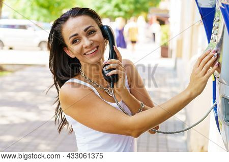 Positive Brunette Woman Holding Telephone Receiver Calls Through Stationery Phone In Street, Tourist