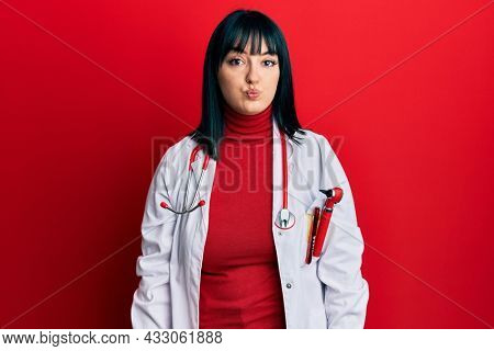 Young hispanic woman wearing doctor uniform and stethoscope puffing cheeks with funny face. mouth inflated with air, crazy expression.