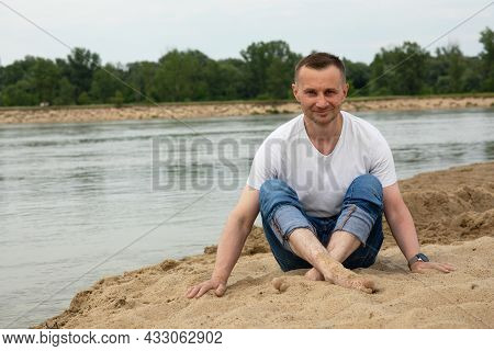 The Image Lonely Positive And Smile Man Sitting On The Beach River