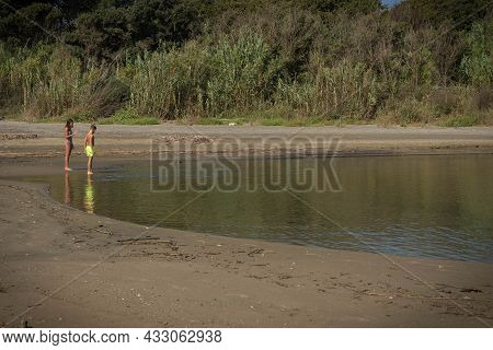 Two And Their Reflection In The River Flowing Into The Sea At Torre Astura In Italy