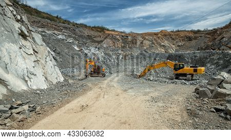 Heavy Machinery (excavator, Hydraulic Hammer) In An Open Pit Stone Quarry.