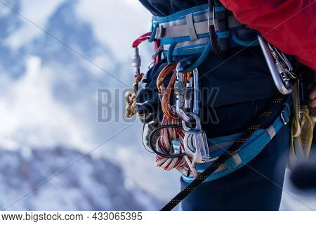 Young Man Traveler Alpinist Climbs To The Top Of A Snowy Mountain With Climbing Equipment, Harness,