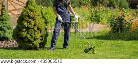 A Young Man Is Mowing A Lawn With A Lawn Mower In His Beautiful Green Floral Summer Garden. A Man Wi