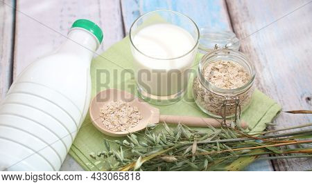 Close-up Of A Glass And A Bottle With Oat Milk, Oat Spikelets, And A Wooden Spoon With Oat Flakes On