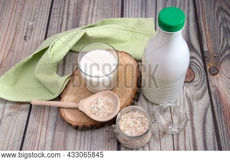 An Alternative To Traditional Milk Is Vegan Oat Milk In A Glass With A Wooden Spoon With Oat Flakes