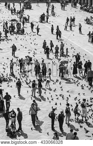 Venice, Italy - April 11, 2007: Tourists On San Marco Square Feed Large Flock Of Pigeons. San Marco