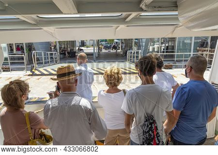 Venice, Italy - July 5 2021: The Ferry Anchors At The Ferry Stop Lido With Tourists And Local People