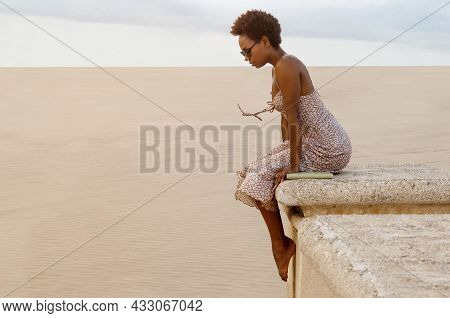 Woman With Sunglasses And Afro Sitting On A Wall With A Book Beside Her. Concept Of Peace And Sereni