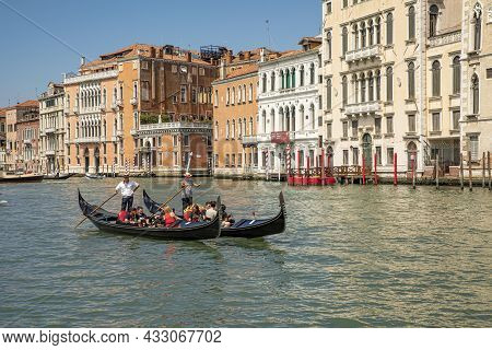Venice, Italy - July 1, 2021: People Enjoy The Gondola Ride At Canale Grande In Classical Hand Drive
