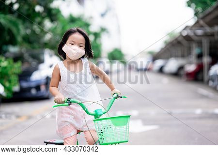 Happy Child Girl Rides A Bicycle On The Road Around Her House In The Evening Time. Kid Wearing Cloth