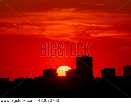 Burgundy Sunset Over The City. The Bright Sun Sets Between High-rise Buildings. Cityscape At Sunset.