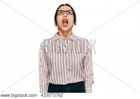 Young hispanic girl wearing casual clothes and glasses angry and mad screaming frustrated and furious, shouting with anger. rage and aggressive concept.