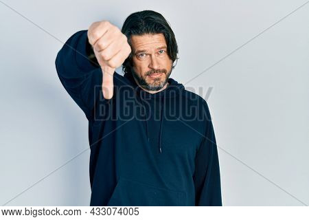 Middle age caucasian man wearing casual sweatshirt looking unhappy and angry showing rejection and negative with thumbs down gesture. bad expression.