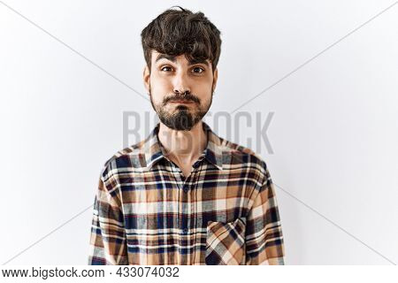 Hispanic man with beard standing over isolated background puffing cheeks with funny face. mouth inflated with air, crazy expression.